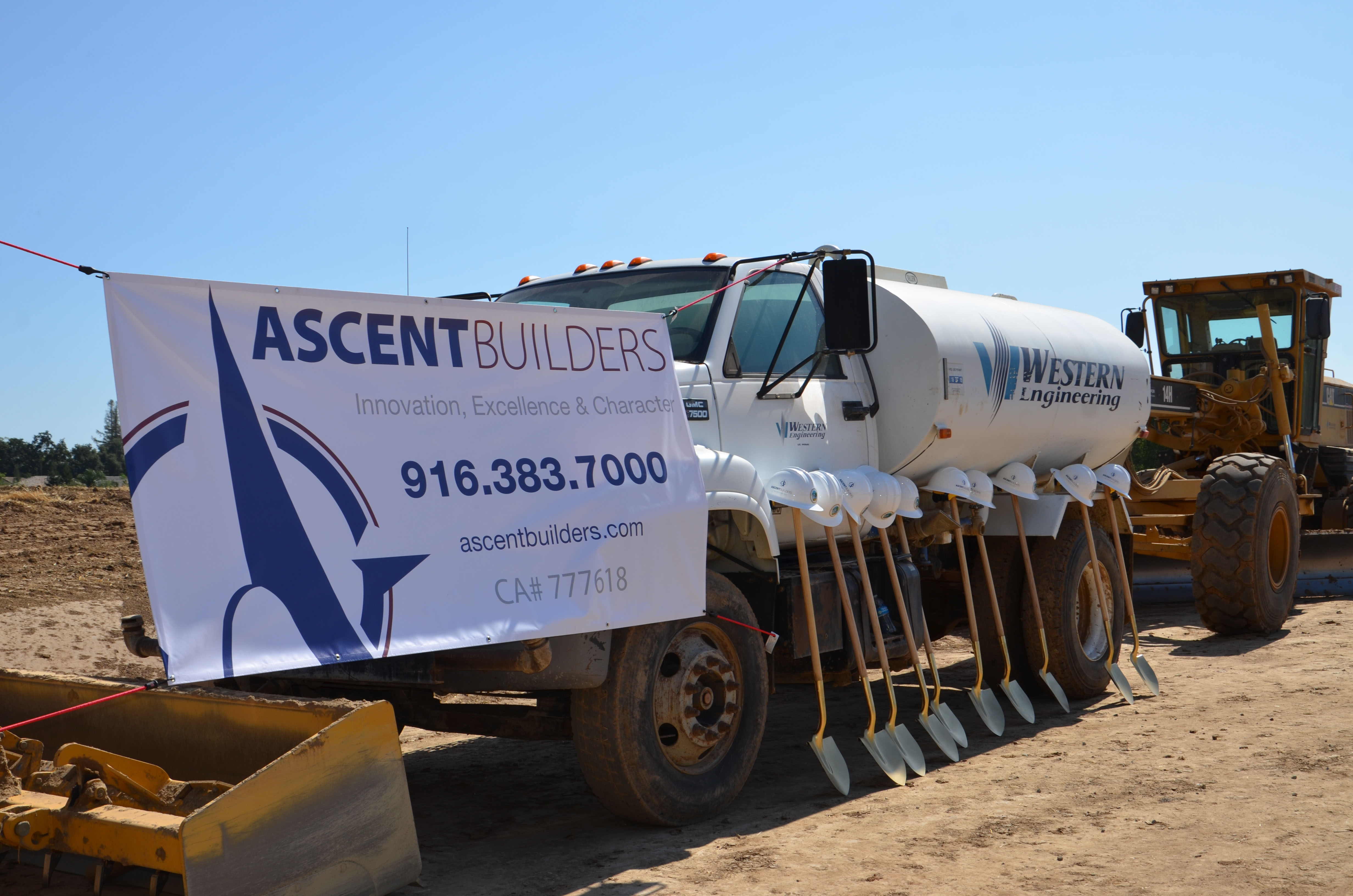 The groundbreaking shovels and hardhats lined up in front of Ascent Builders trucks